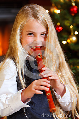 Girl playing recorder on christmas eve