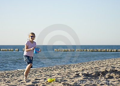 Girl playing on sandy beach