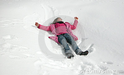 Girl playing in snow during wintertime