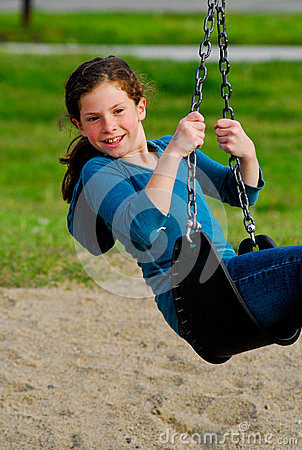 Girl playing on a swing.