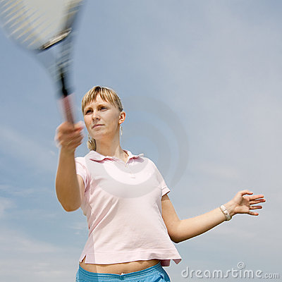 Girl playing tennis on background of sky