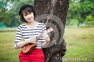 Girl playing Ukulele in park outdoor