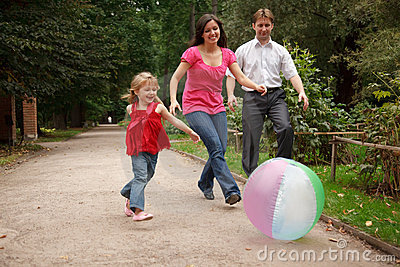 Girl plays with big ball in park with parents