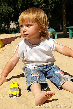 Free Girl Plays Sand On A Beach Royalty Free Stock Image - 5908106