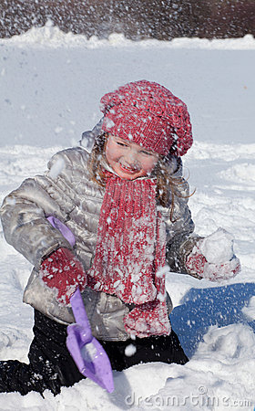 The girl plays on snow