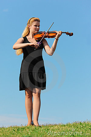 Girl plays violin against  sky