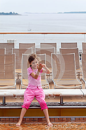Girl plays with water on deck of ship.