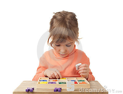 Girl plays in wooden figures in form of numerals