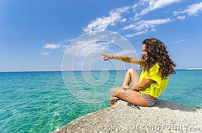 Girl pointing to ocean horizon