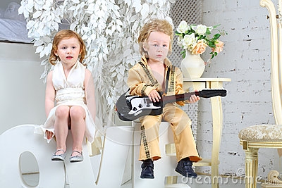 Girl and pop musician with guitar sit on letters