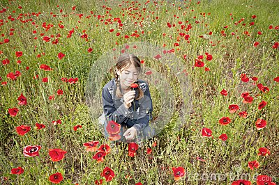 Girl with poppies squatting & smelling wide