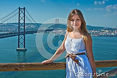 Girl posing and the April 25 bridge in Lisbo