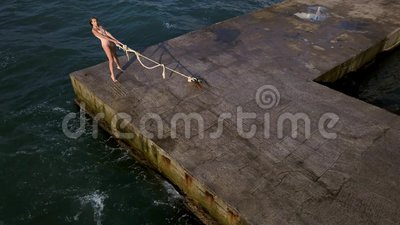 girl posing seafront nice ballerina light leotard pulling rope standing toes concrete pier stormy sea 120349765