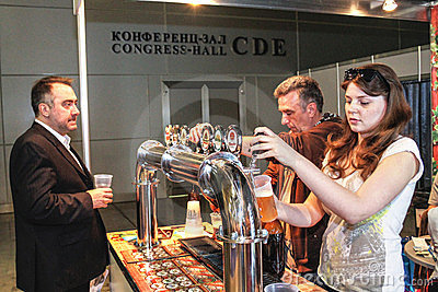 Girl pouring beer to glass from beer tap Editorial Stock Photo