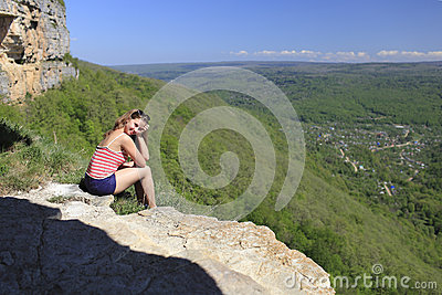 Girl at the precipice in the mountains