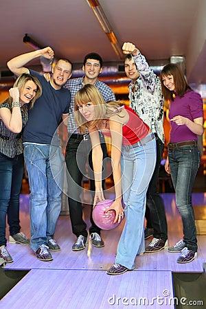 Girl prepares throw ball in bowling club