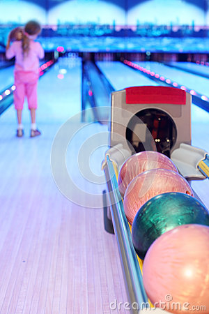 Girl prepares to throw ball in bowling