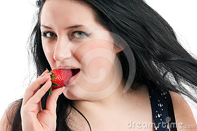 The girl presses a strawberry to the lips