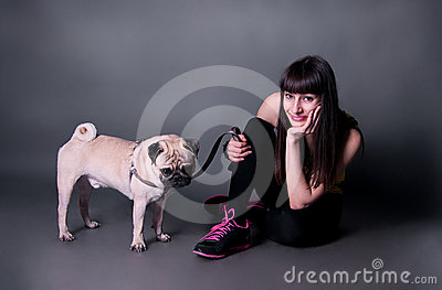 Girl with pug dog in studio