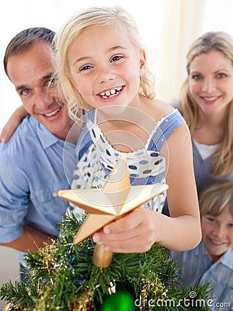 The girl put the Christmas star on top the tree