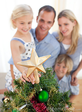 The girl put the Christmas star on top of the tree