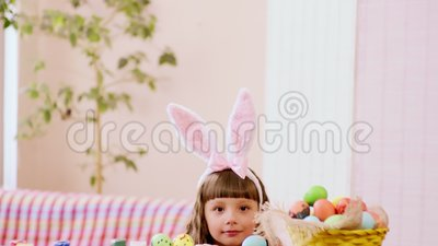 girl-rabbit-ears-looks-out-behind-table-which-stands-basket-easter-eggs-141107396
