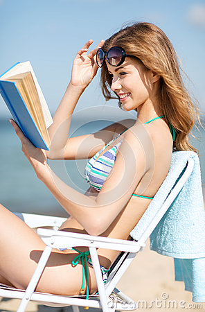 Girl reading book on the beach chair