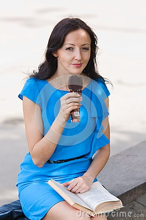 Girl reading a book eating ice cream