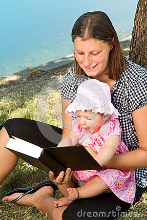 Girl reading book with her mother