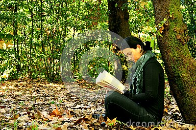 Girl reading a book in a park