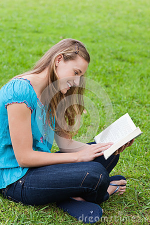 Girl reading a book while sitting down in a park