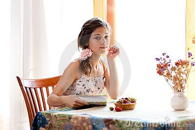 Girl reading book sitting at table with strawberry