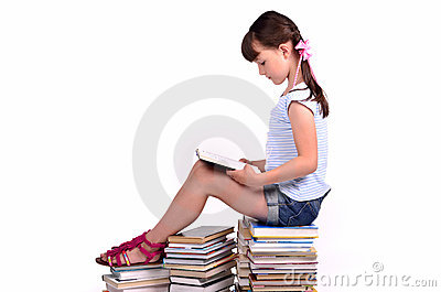 Girl reading a booksitting on big pile of books