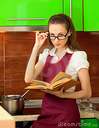 Girl reading a cookbook on kitchen