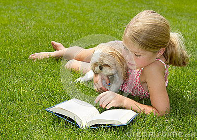 Girl reading with dog outdoors