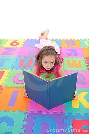 Girl reading kids book lying on alphabet floor mat