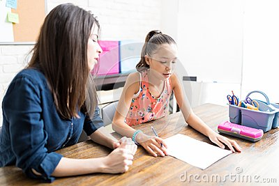 Girl Reading Lesson On Paper By Private Tutor At Table Stock Photo
