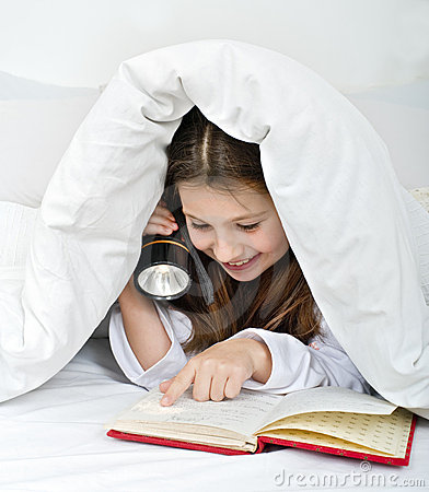 Girl reading under blanket