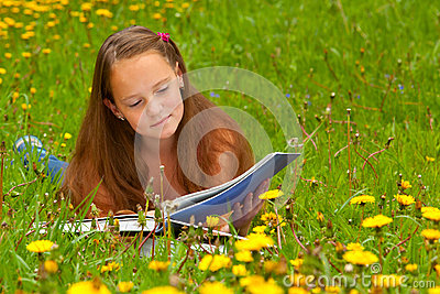 A girl reads a book in the meadow