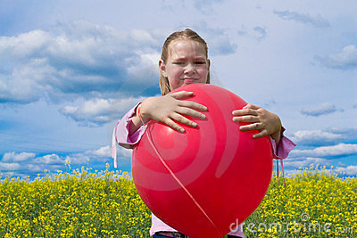 Girl with red balloon in meadow