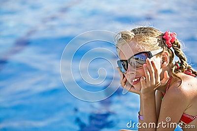 Girl in red bikini, glasses near  swimming pool.