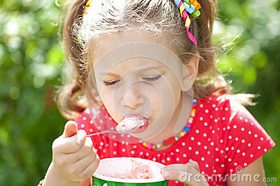 Girl in a red blouse with relish eating ice cream