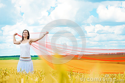 Girl with a red cloth catches wind in the field