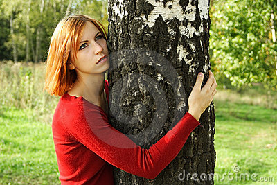 Girl in red dress hug a tree, looking at side