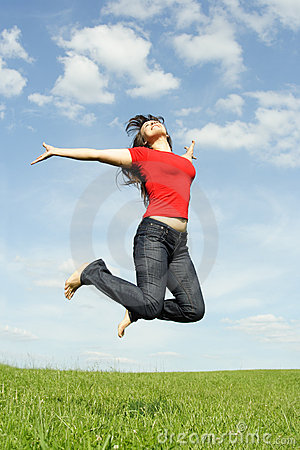 Girl in red shirt jumping on summer meadow