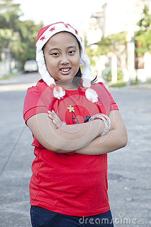 Girl in red shirt and santa hat standing on the village street