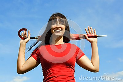 Girl in red shirt with umbrella, blue sky