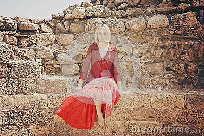 Girl in red sitting on the wall