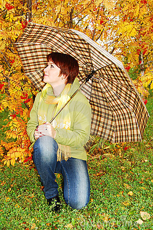 Girl and red umbrella in the autumn park.