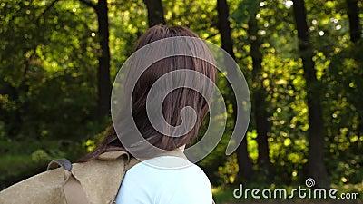 Girl-Reisende mit Rucksack wandern entlang einer Waldstraße Wanderer wandert im Sommer im Wald glückliche Wanderer stock video